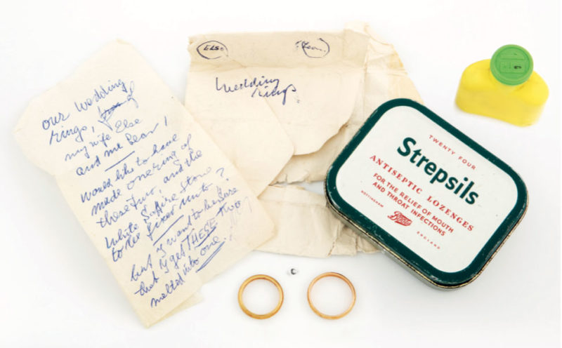 A tin, two wedding rings, a sapphire, and a note,