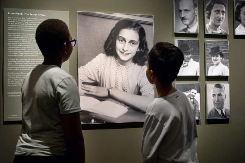 Students in the Auschwitz exhibition looking at a photo of Anne Frank