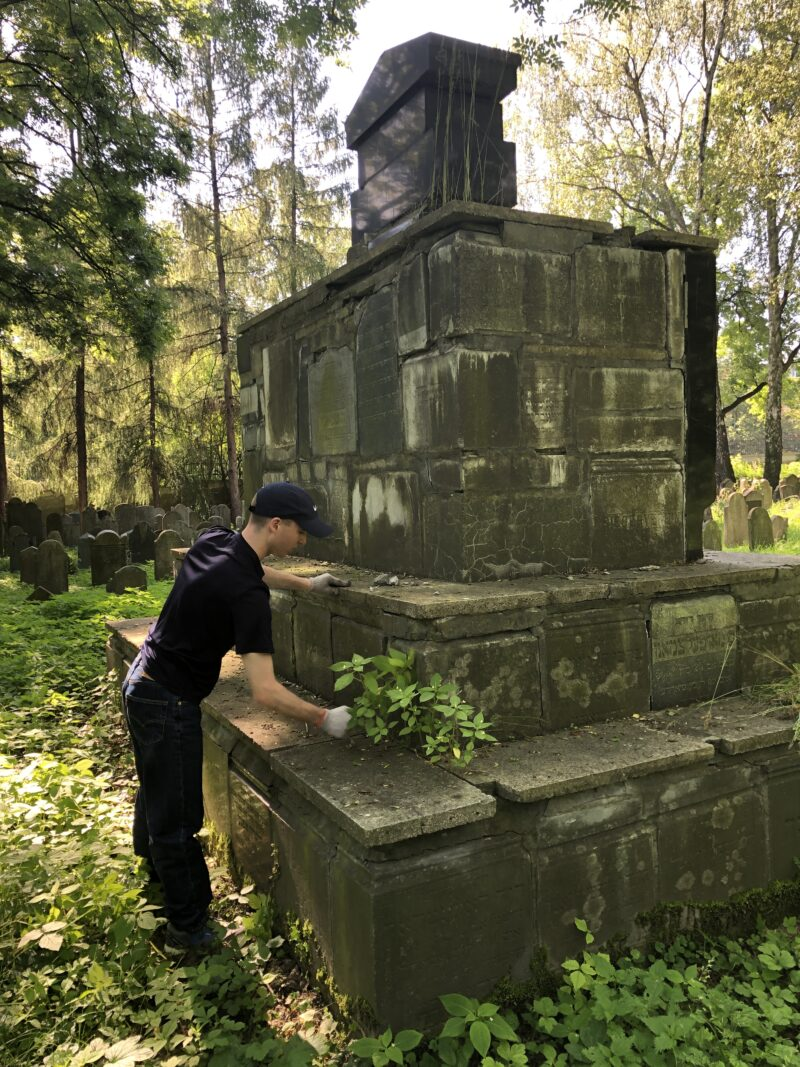 A US Coast Guard Academy cadet participating in the AJC American Service Academies Program participant cleans one of the monuments erected of broken tombstones in the Jewish cemetery.