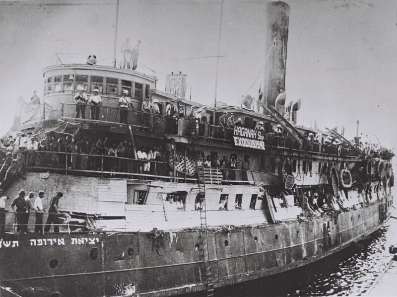 """Exodus ship following British takeover (note damage to makeshift barriers). Banner says: """"HAGANAH Ship EXODUS 1947""""."""
